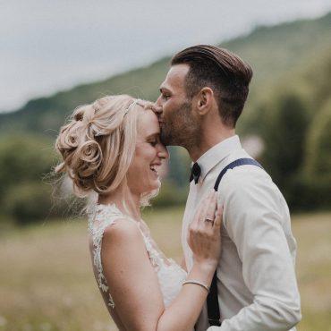 Stirnkuss des Brautpaares in ländlicher Umgebung