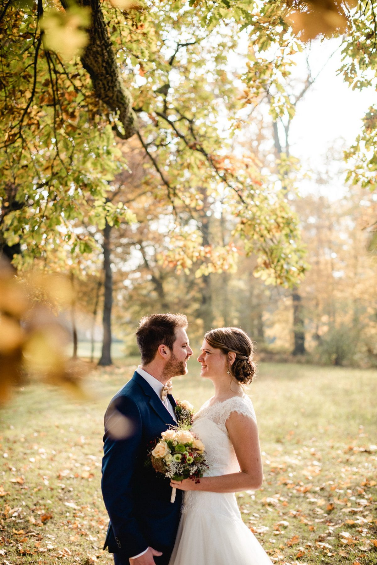 Herbst Bäume Blätter Äste Sonne Paar Blumenstrauß Liebe Augenblick Anzug