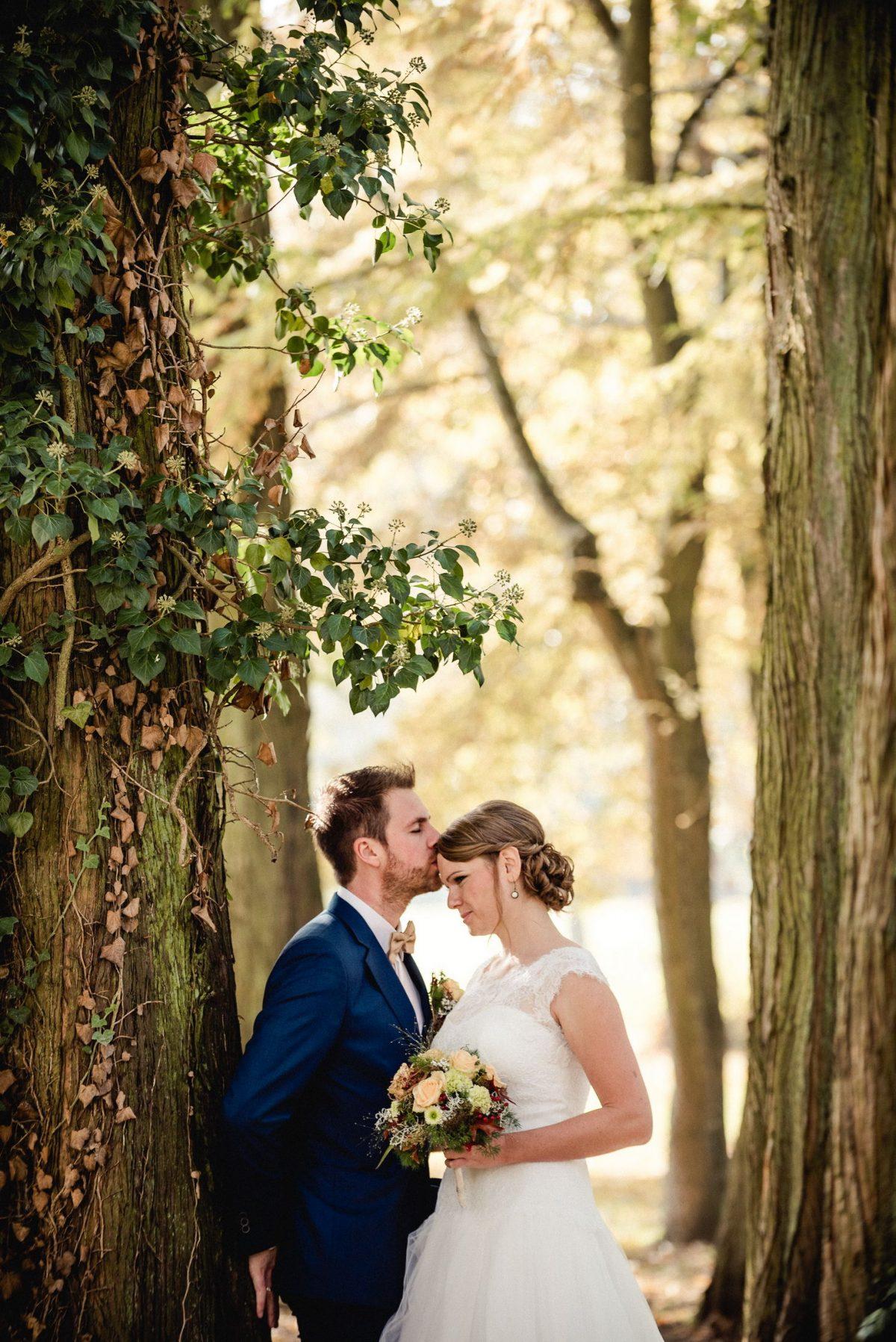Kuss Liebe Brautkleid Anzug Blau Herbst Blätter Bäume Frisur Ohrringe Fliege Blumen