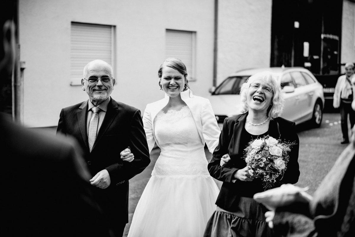 Brauteltern Mama Papa Braut Kleid weiß Lachen Witz Brautstrauß Blumen Gäste