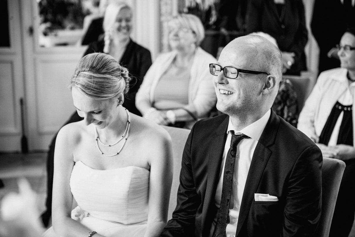 Lachen Gäste Trauung Hochzeit Brautpaar Kleid Kette Schmuck Krawatte Brille Frisur