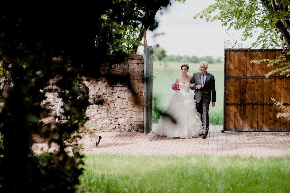 Hochzeit Vater Tochter Tor Wiese Brautstrauß Hochzeitskleid