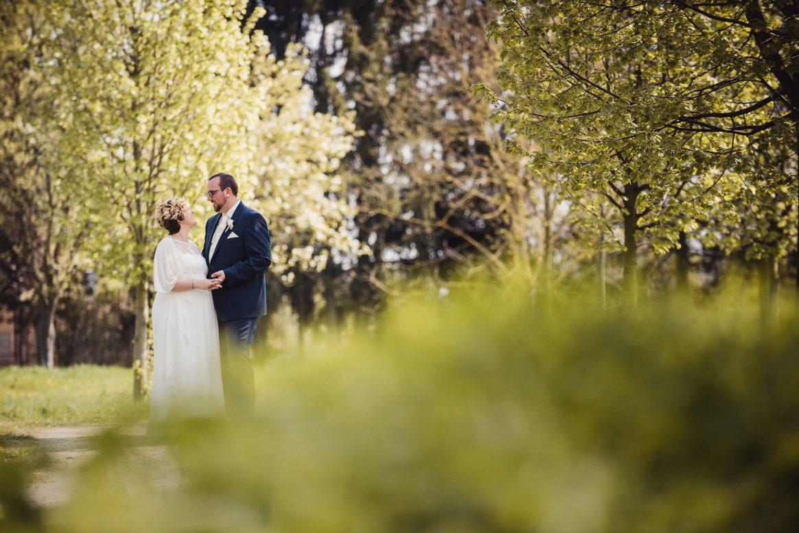 Ehepaar Hochzeit Mann Frau weiß Kleid Umarmung Park grün Shooting