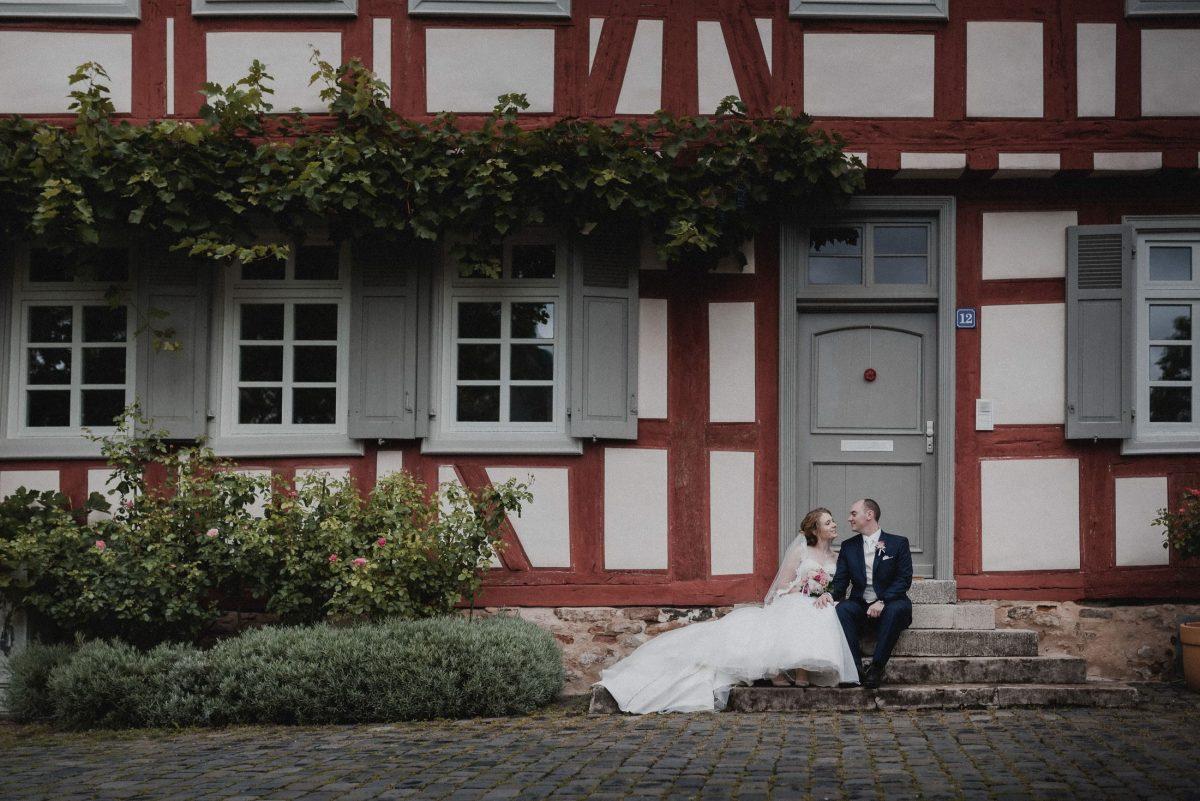 Fachwerkhaus rot weiß blühende Büsche Treppe sitzen Blicke
