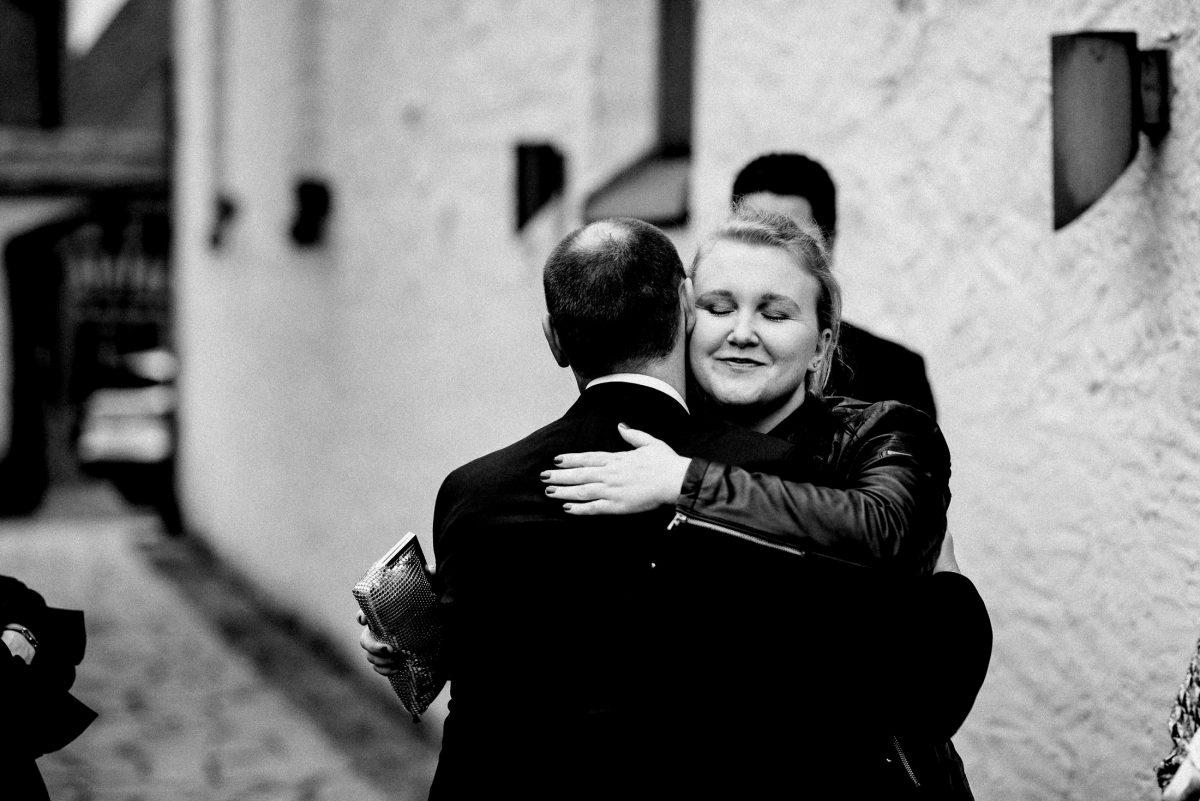 Begrüßung umarmung Kirchenmauer außen Mann Frau