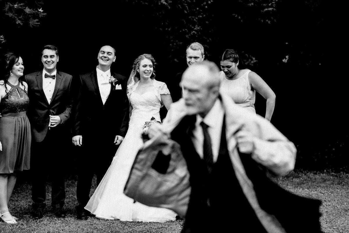 Gruppenfoto Brautpaar Wiese lachen unscharfer Mann