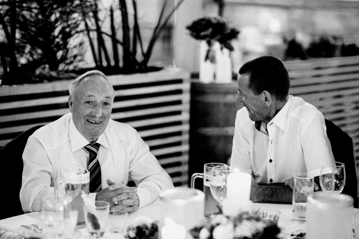 Biergläser lachen Männer Tisch Holzfass Blumen