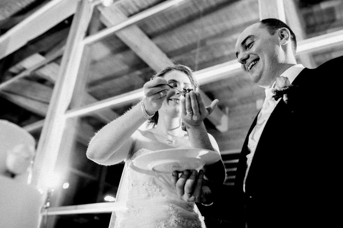 Bräutigam füttern Hochzeitstorte Hände Teller Gabel