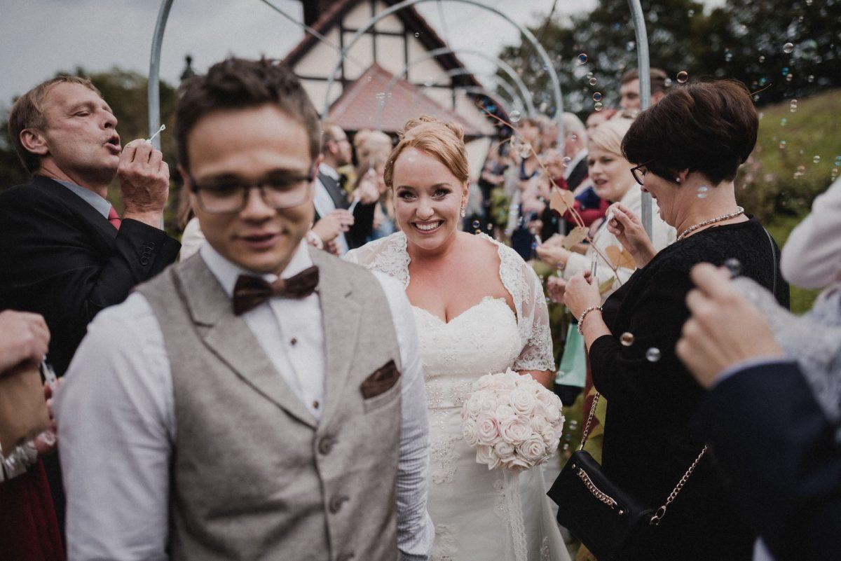 Spalier stehen Brautpaar Brautstrauss Fliege Weste Gäste Kapelle