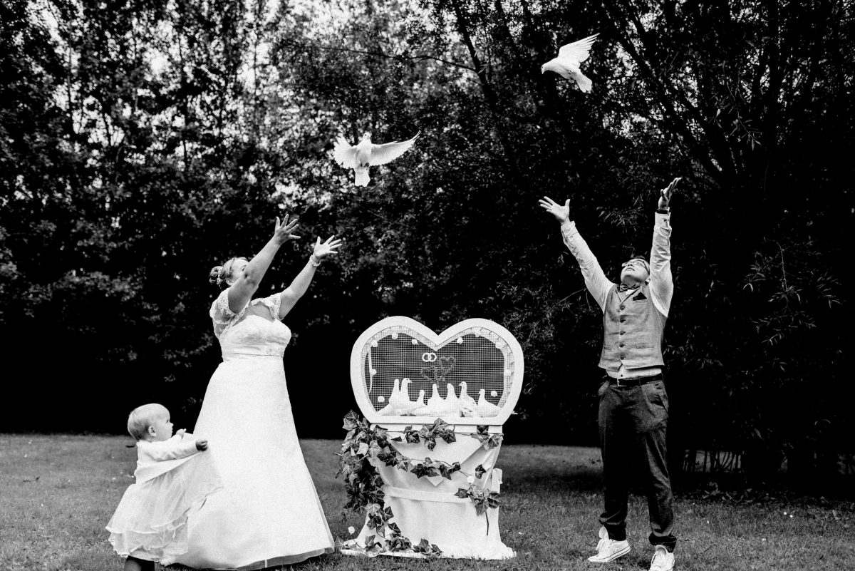Brautpaar Kind Familie weiße Tauben Tauben fliegen lassen Bäume