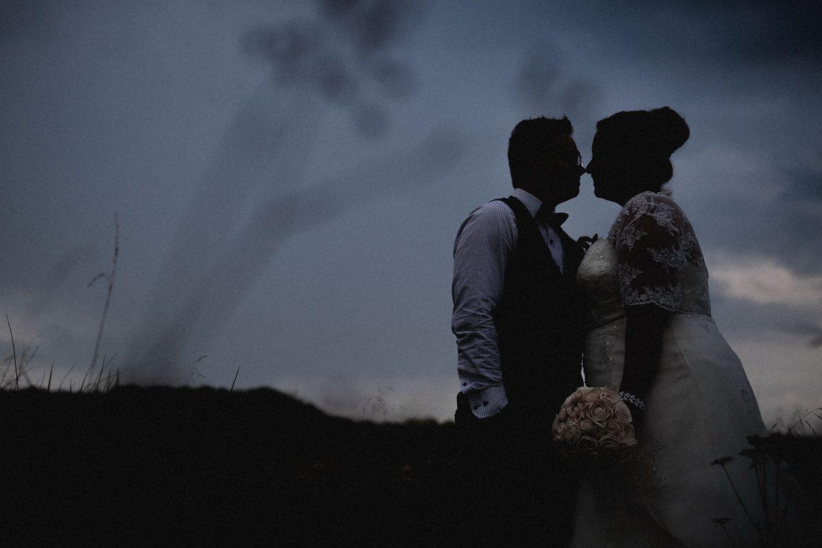 Sonnenuntergang Braut Bräutigam Kuss Brautstrauss Wiese zweisamkeit