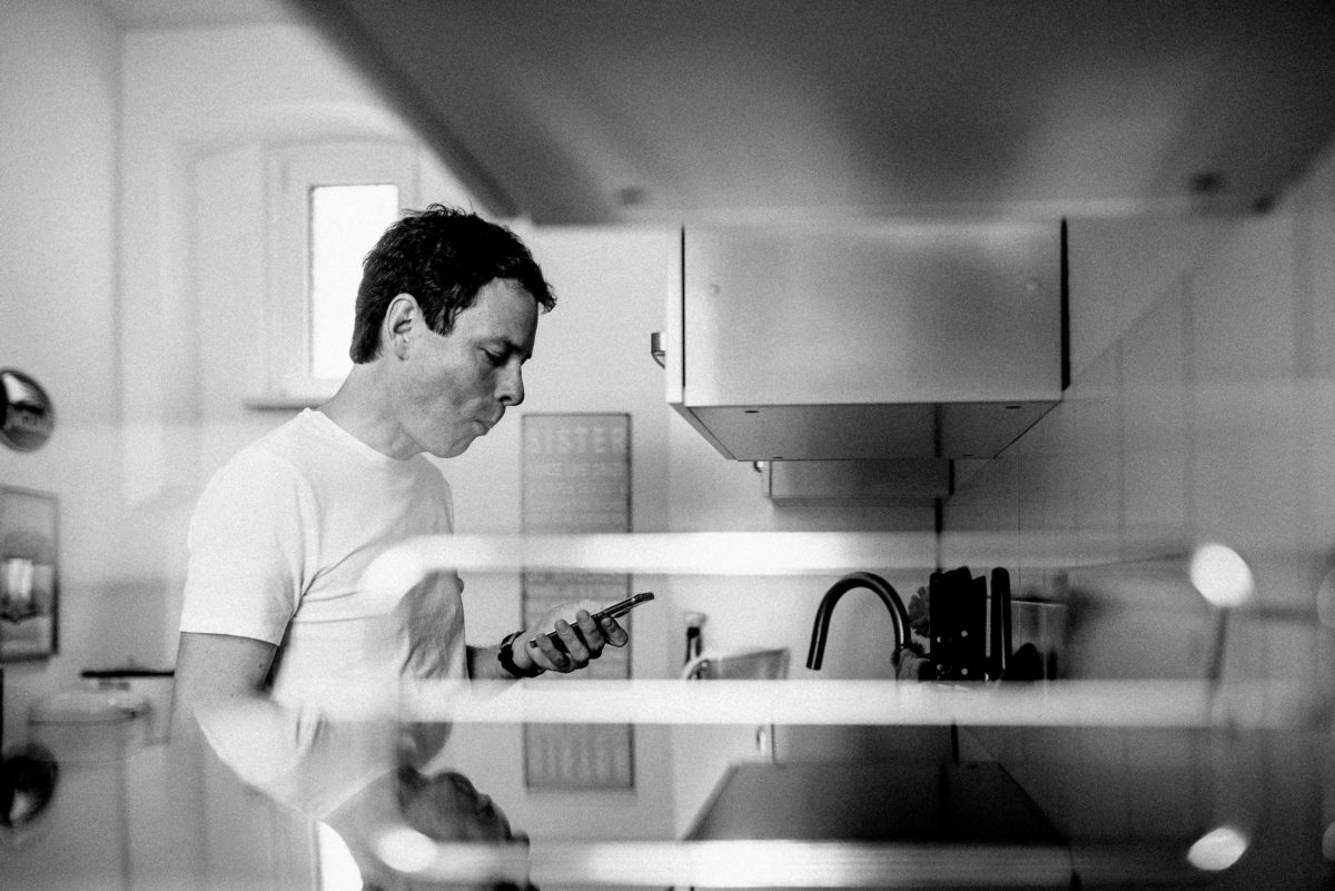 Küche,Mann,Handy,Hängeschränke