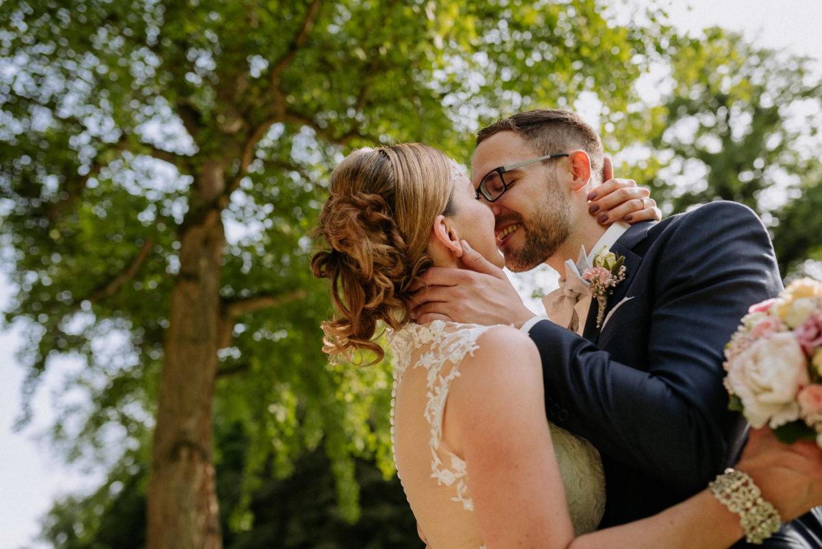 Kuss,frisch verheiratet,Rückenfreies Brautkleid mit spitze,Baum