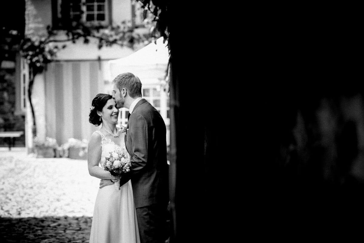Stirnkuss,Brautpaar,Steinmauer,Blumenranken