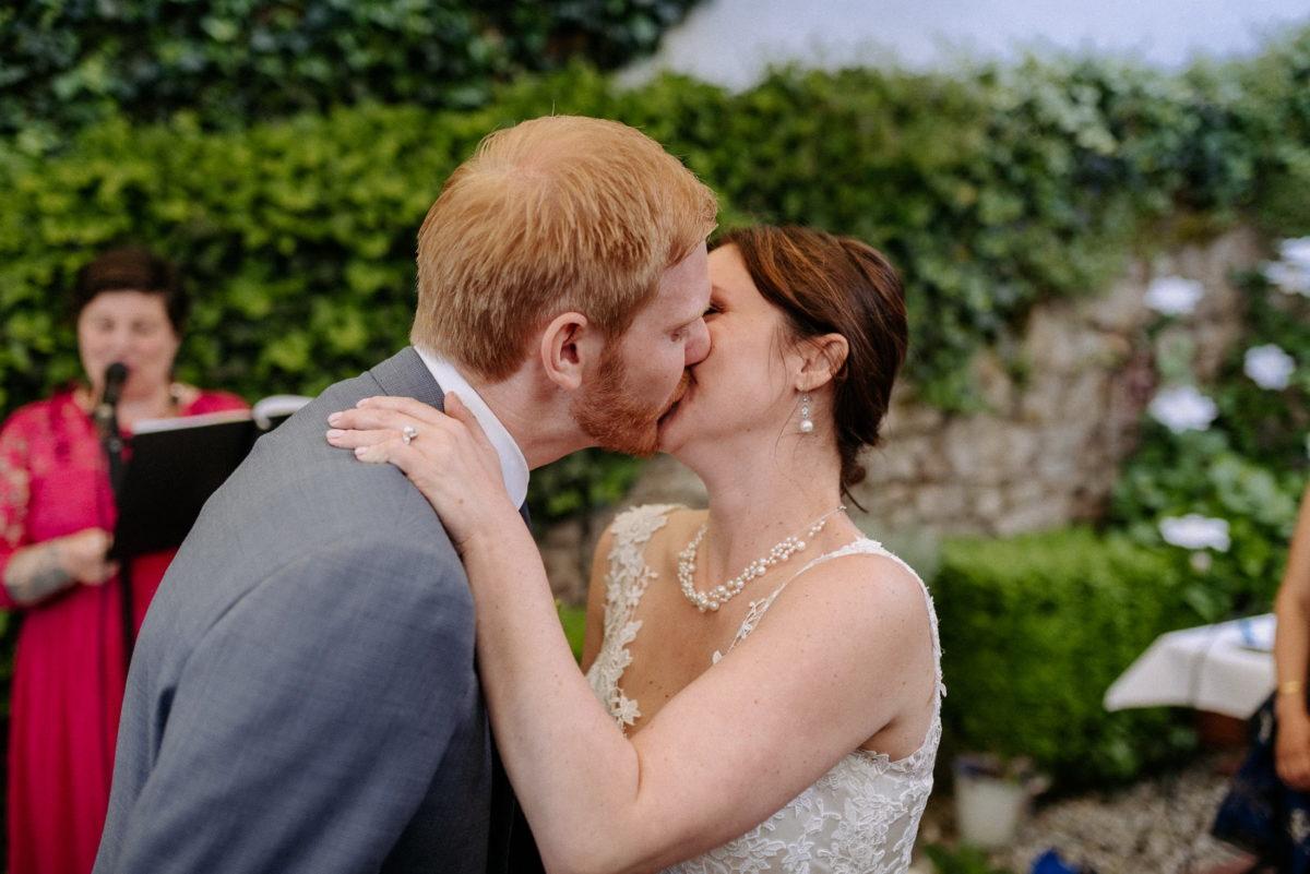 erster Kuss,frisch vermähltes Ehepaar,Halskette,Efeuranken,Steinmauer