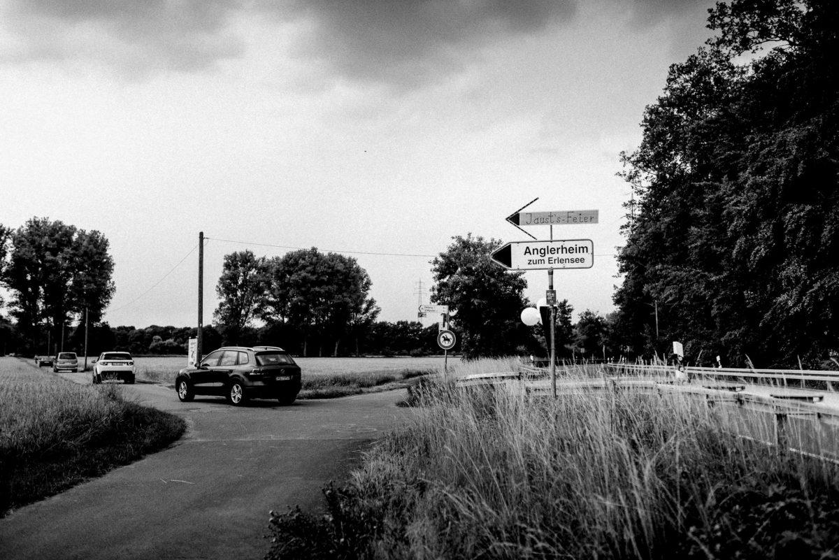Anglerheim zum Erlensee,Autos,Wiese,Bäume,Wegweiser