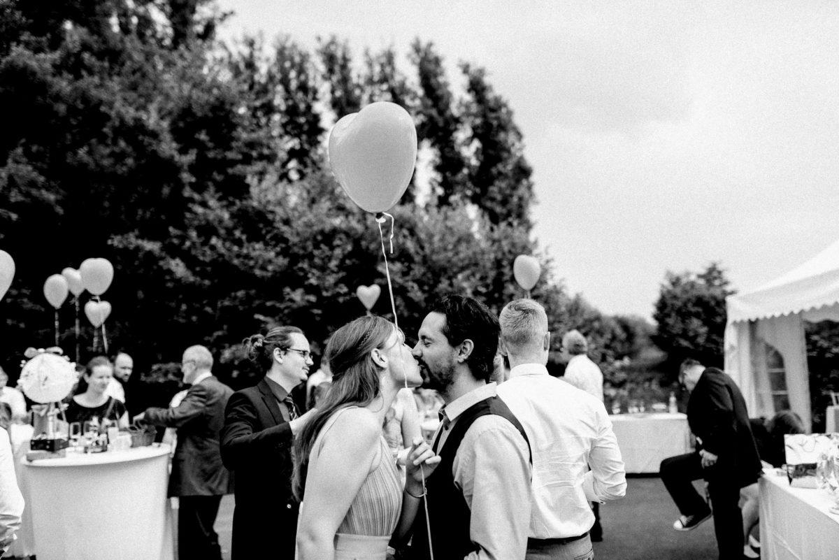 Kuss,Herzballons,Stehtische,Hussen,Bäume,Hochzeitsgesellschaft