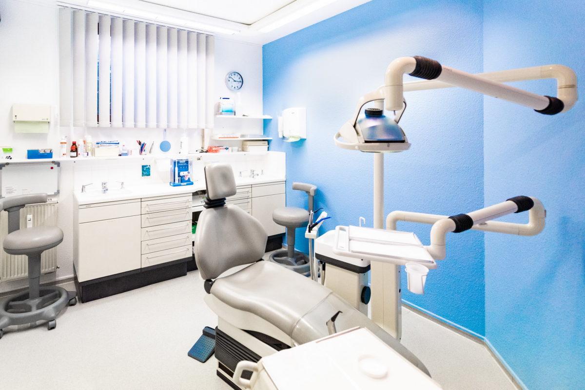 Behandlungsraum,Zahnarztstuhl,blaue Wand,Wanduhr,