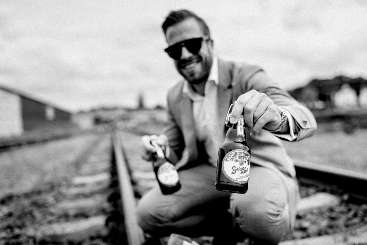 Schlappe SeppelBier,Bierflaschen,Bahngleis,Mann,Sonnenbrille