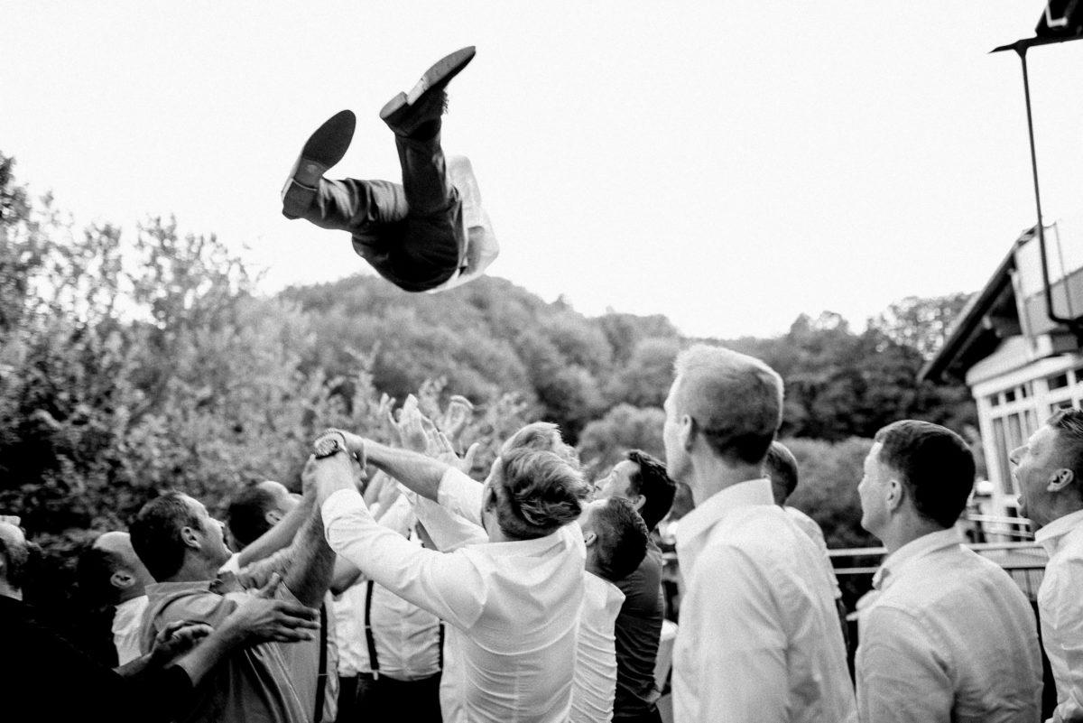 Männergruppe,Bräutigam werfen,Hochzeitsfeier