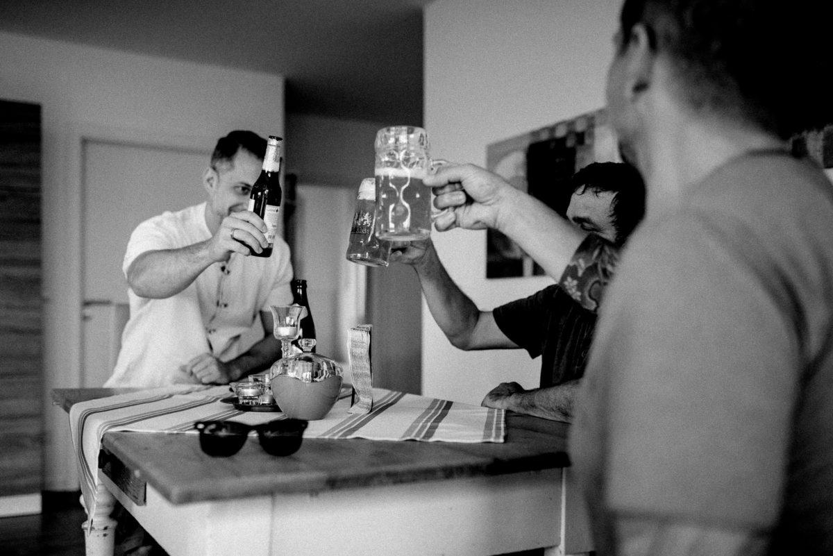 Männer,anstoßen,Bier trinken,Esszimmertisch,