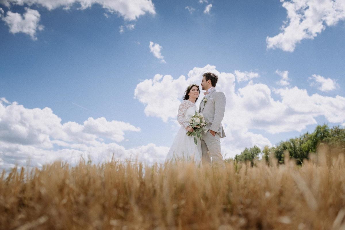 Lächeln, blauer Himmel, Wolkenformation, Feld, Bäume, Paar, Blumen, Strauß, Hochzeit, heiraten