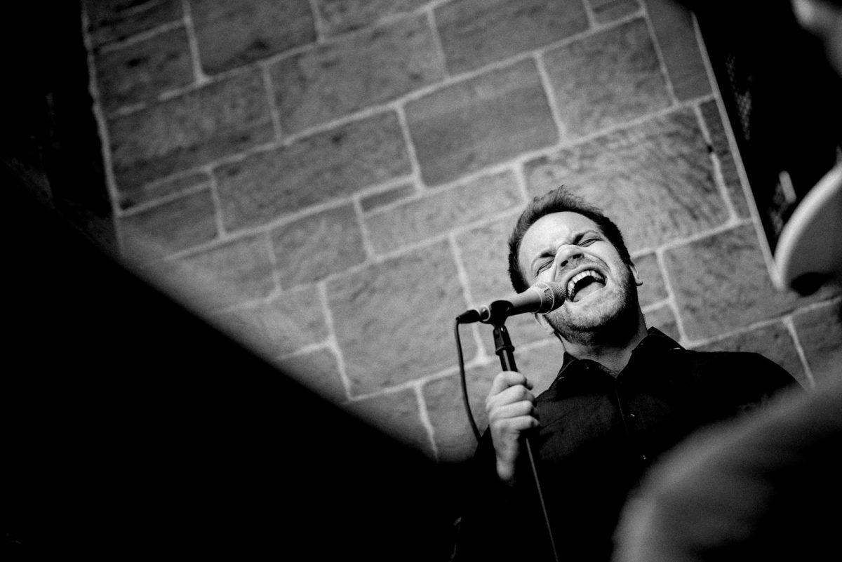 singen, Sänger, Mikrofon, Mauer, schwarzes Hemd