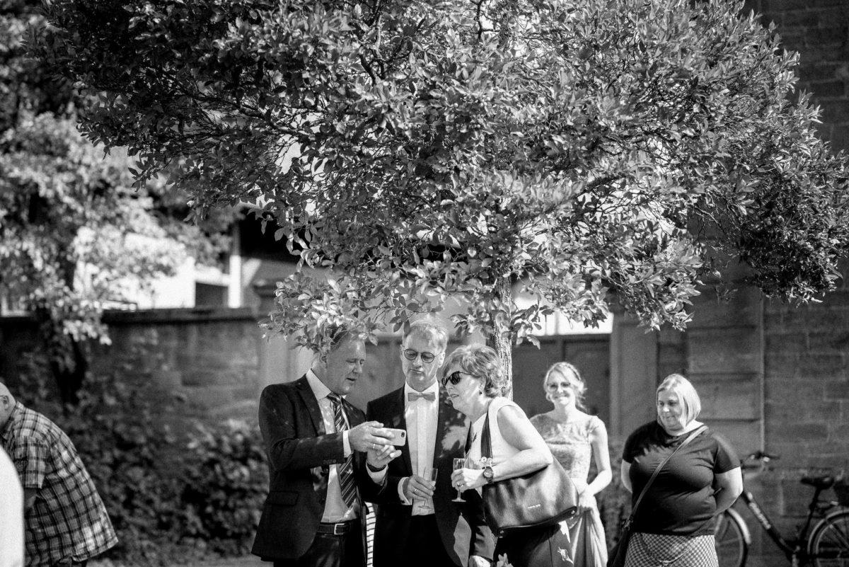 Hochzeitsfotografie, schwarzweiß, heiraten, Gäste, Handy, reden, Sekt