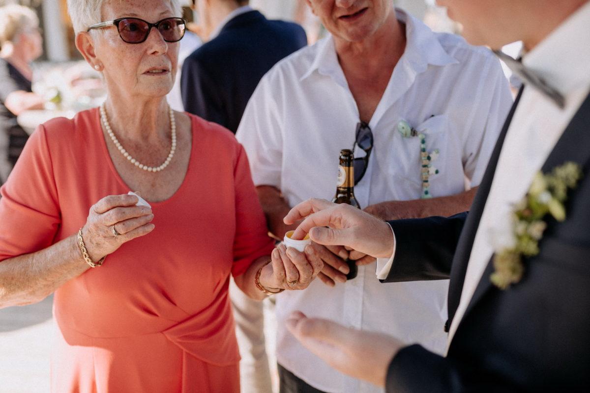 Hochzeitsfotografie, Gäste, rotes Kleid, Perlenkette